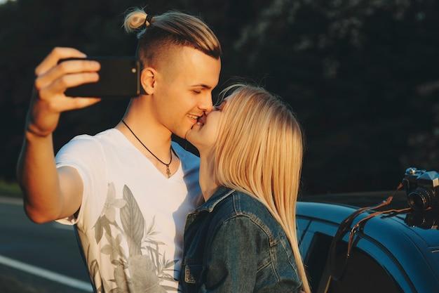 Vista lateral de um homem bonito beijando uma mulher loira atraente e recebendo uma selfie na câmera frontal do smartphone, ambos sorrindo com os olhos fechados e em pé no carro ao pôr do sol