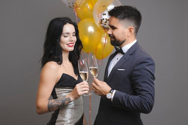 Vista lateral de um homem bonito de terno e uma linda mulher de vestido de noite sorrindo e tilintando taças de champanhe em pé perto de um monte de balões no fundo cinza
