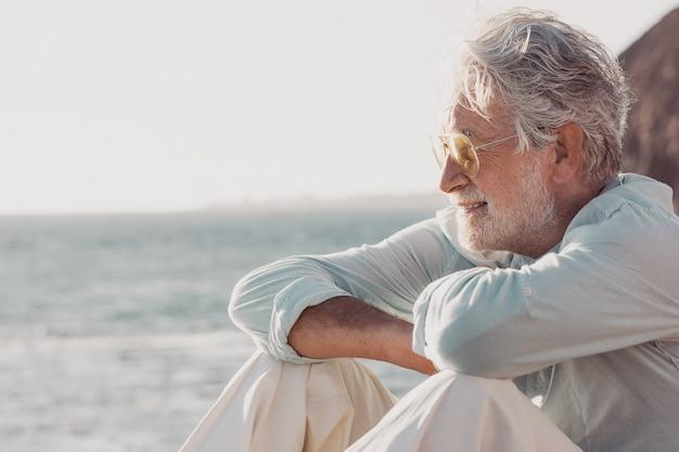 Vista lateral de um homem bonito sênior, de cabelos brancos, sentado na praia, olhando o horizonte sobre a água