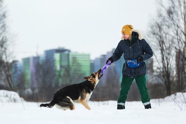 Vista lateral de um homem brincando com um cão pastor no campo de inverno