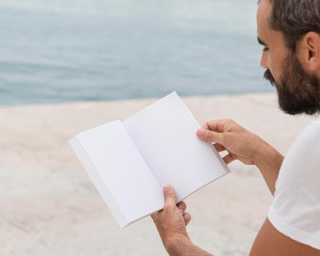 Vista lateral de um homem com barba lendo ao ar livre