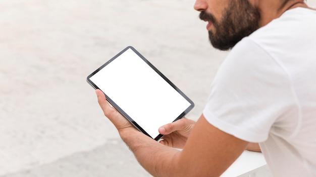 Vista lateral de um homem com barba segurando o tablet ao ar livre