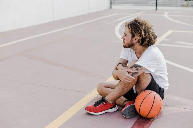 Vista lateral, de, um, homem, com, basquetebol, sentando, em, corte