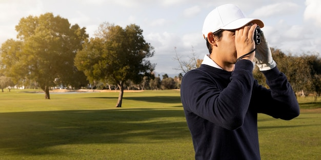 Vista lateral de um homem com binóculos no campo de golfe
