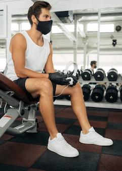 Vista lateral de um homem com máscara médica e fones de ouvido na academia