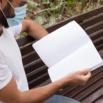 Vista lateral de um homem com máscara médica lendo livro na bancada