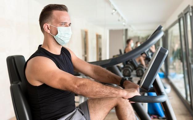 Vista lateral de um homem com máscara médica malhando na academia