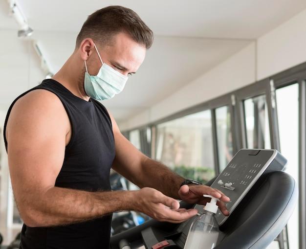 Vista lateral de um homem com máscara médica na academia usando desinfetante para as mãos