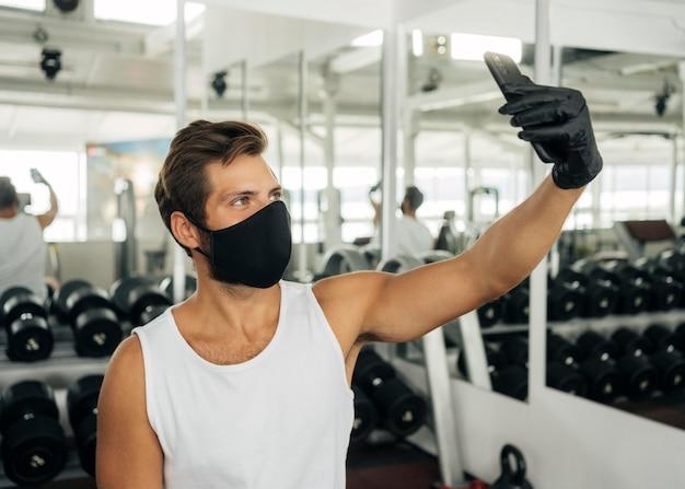 Vista lateral de um homem com máscara médica tirando uma selfie na academia