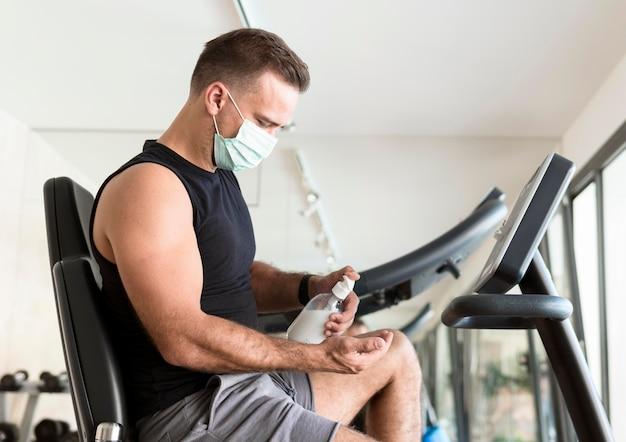Vista lateral de um homem com máscara médica usando desinfetante para as mãos na academia