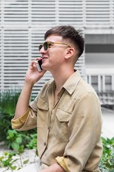 Vista lateral de um homem com óculos de sol falando ao telefone ao ar livre