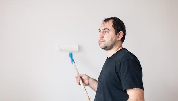 Vista lateral de um homem com rolo pintando uma parede de branco
