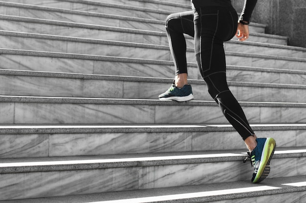 Vista lateral de um homem com roupa esportiva se exercitando nas escadas ao ar livre
