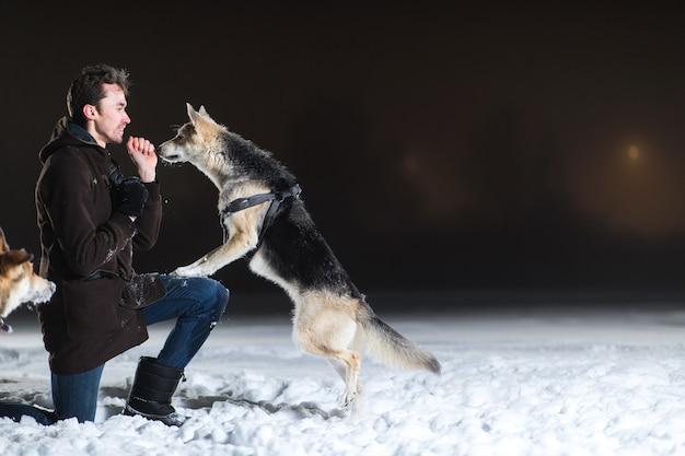 Vista lateral de um homem com um cachorro sem raça definida do lado de fora à noite no inverno
