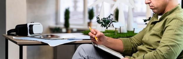 Vista lateral de um homem com uma prancheta pesquisando um projeto de energia eólica ecologicamente correto