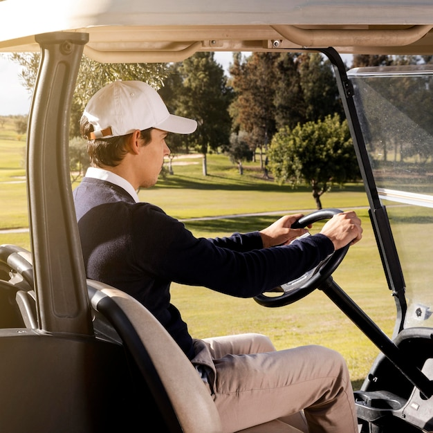 Vista lateral de um homem dirigindo um carrinho de golfe no campo