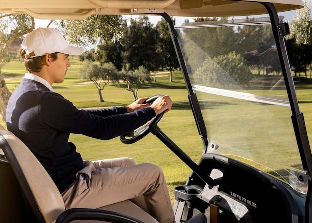 Vista lateral de um homem dirigindo um carrinho de golfe
