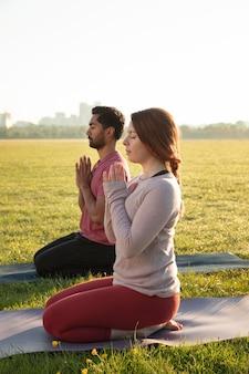 Vista lateral de um homem e uma mulher meditando ao ar livre em esteiras de ioga