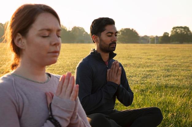 Vista lateral de um homem e uma mulher meditando ao ar livre