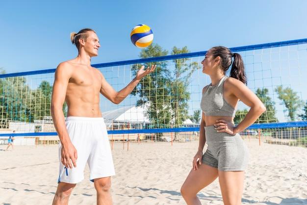 Vista lateral de um homem e uma mulher na praia jogando vôlei