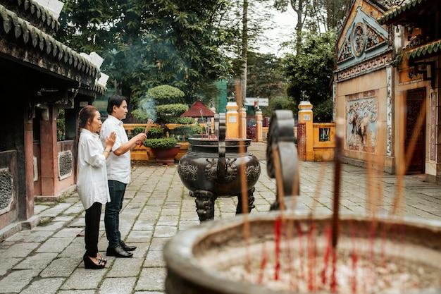Vista lateral de um homem e uma mulher orando no templo com incenso queimando