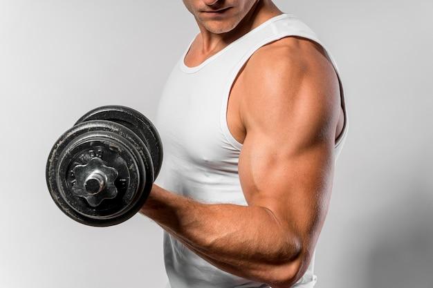Vista lateral de um homem em forma com regata mostrando os bíceps enquanto segura o peso