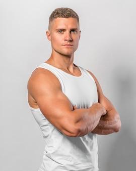 Vista lateral de um homem em forma posando com uma camiseta regata com os braços cruzados