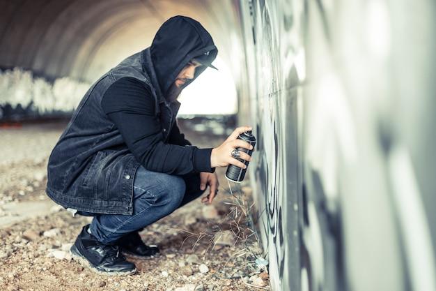 Vista lateral, de, um, homem, em, hoodie, quadro, ligado, graffiti, parede