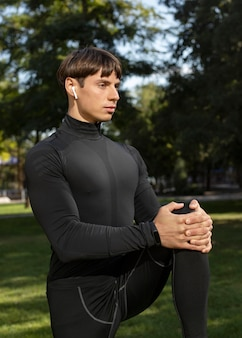 Vista lateral de um homem em roupas esportivas e fones de ouvido ao ar livre
