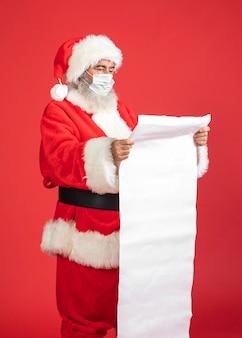 Vista lateral de um homem fantasiado de papai noel com máscara médica segurando uma lista de presentes