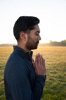 Vista lateral de um homem fazendo ioga ao ar livre