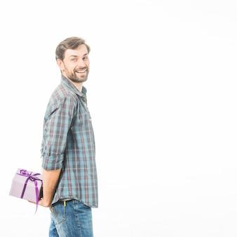 Vista lateral de um homem feliz, segurando a caixa de presente em fundo branco