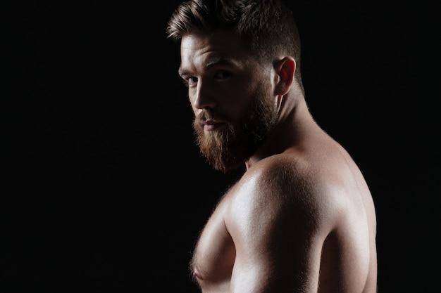 Vista lateral de um homem forte nu. fundo escuro isolado