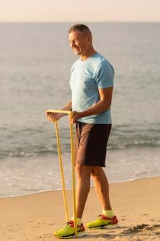 Vista lateral de um homem idoso com corda elástica na praia