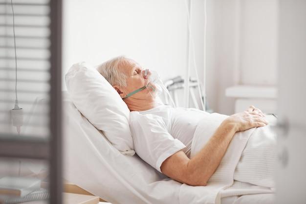 Vista lateral de um homem idoso doente, deitado em uma cama de hospital com máscara de suplementação de oxigênio e olhos fechados, copie o espaço