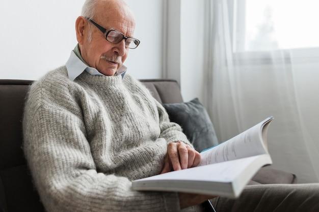 Vista lateral de um homem idoso em uma casa de repouso lendo um livro