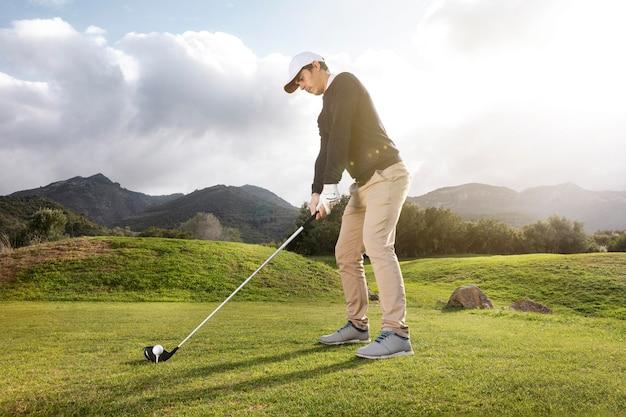 Vista lateral de um homem jogando golfe no campo com o taco