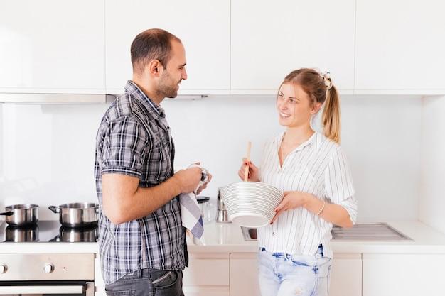 Vista lateral, de, um, homem jovem, ajudando, seu, esposa, preparando alimento, cozinha