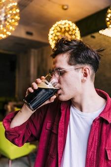 Vista lateral, de, um, homem jovem, bebendo cerveja, em, bar