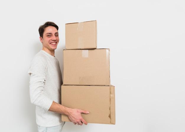 Vista lateral, de, um, homem jovem, carregar, a, pilha, de, caixas cartão, contra, parede branca