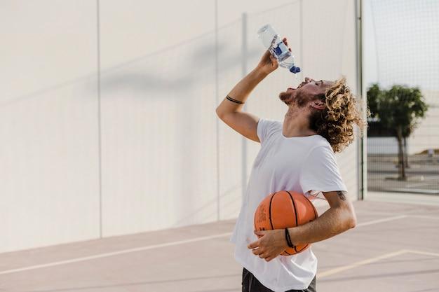 Vista lateral, de, um, homem jovem, com, basquetebol, bebendo, água