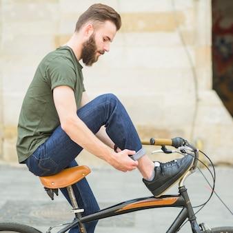 Vista lateral, de, um, homem jovem, com, bicicleta, dobrando, seu, calças brim