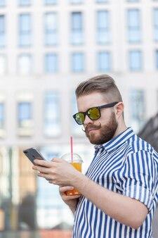 Vista lateral de um homem jovem e elegante hippie com óculos, bigode e suco nas mãos, conversando nas redes sociais usando um smartphone e internet sem fio em um dia quente de verão.