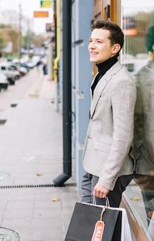 Vista lateral, de, um, homem jovem, em, na moda, paleto, segurando, bolsas para compras, ficar, ligado, rua