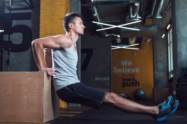 Vista lateral, de, um, homem jovem, exercitar, em, ginásio