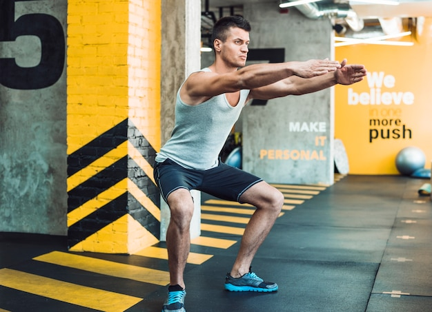 Vista lateral, de, um, homem jovem, fazendo, exercício, em, clube aptidão