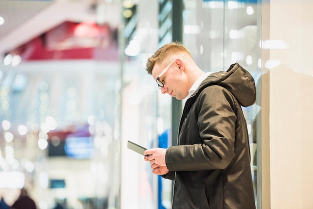 Vista lateral, de, um, homem jovem, ficar, em, a, centro comercial, usando, telefone móvel