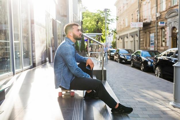 Vista lateral, de, um, homem jovem, relaxante, ligado, skateboard