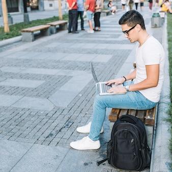 Vista lateral, de, um, homem jovem, sentar-se banco, usando computador portátil