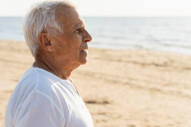 Vista lateral de um homem mais velho apreciando a vista da praia